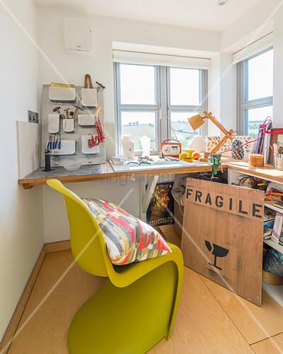 Green designer chair at L-shaped desk below windows