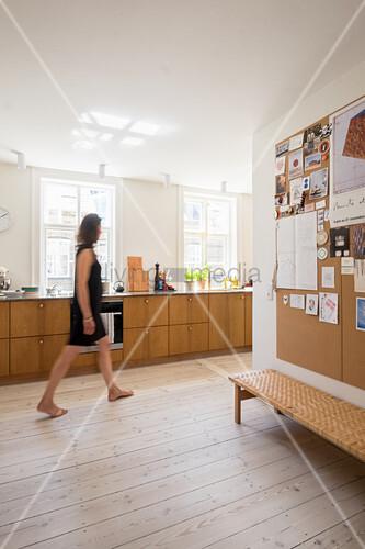 Frau geht barfuß durch offene helle Küche mit Holzfronten