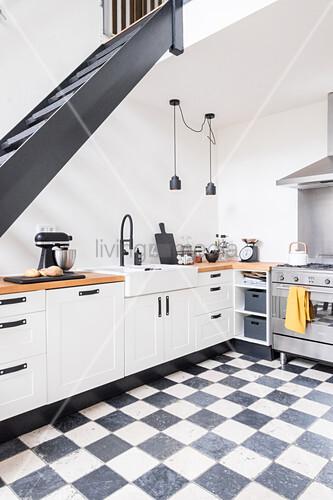 Offene Küche unter der Treppe mit Schachbrettboden