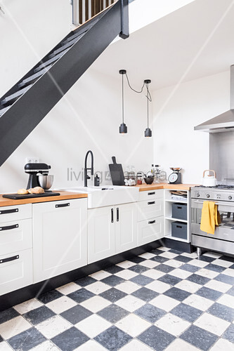 Open-plan kitchen with chequered floor below staircase