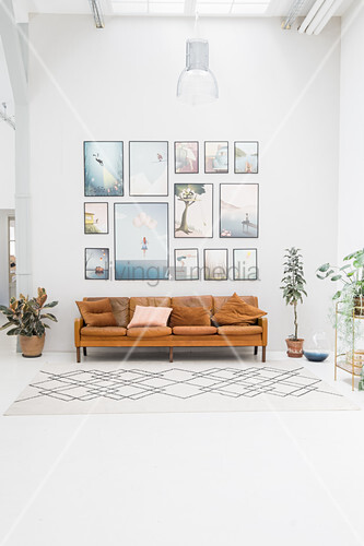 Gallery of pictures above leather sofa in high-ceilinged room