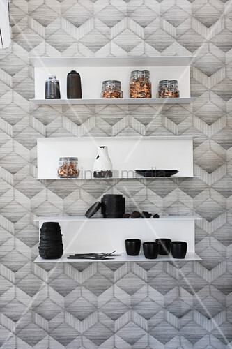 Storage jars, crockery and vases on wall-mounted shelves on monochrome patterned wallpaper
