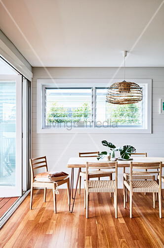 Dining table and chairs on parquet floor next to open terrace doors