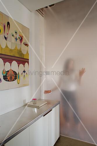 Frau hinter satinierter Glastür