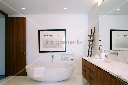 Frei stehende Badewanne und Waschtisch mit Marmorplatte in elegantem Badezimmer