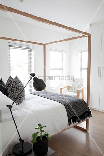 Himmelbett in elegantem Schlafzimmer, im Hintergrund Armlehnstuhl und Einbauschrank