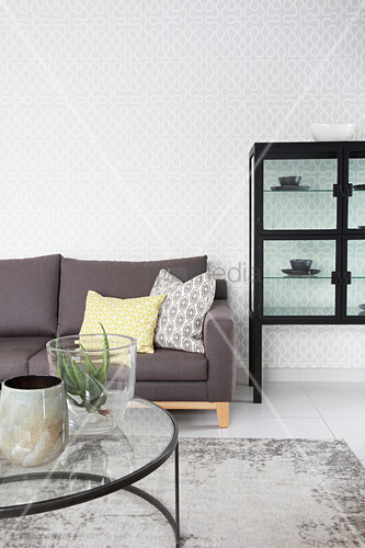 Grey sofa, coffee table with glass top and display case in living room