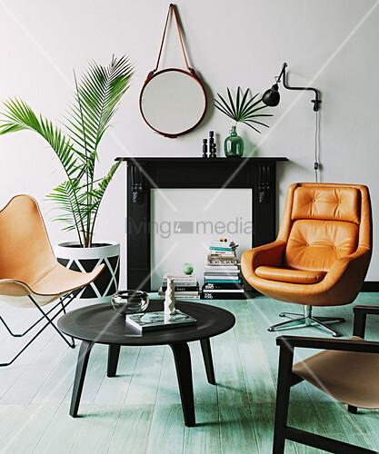 Cognacfarbene Sitzmöbel vor Kamin-Attrappe, Coffeetable und Zimmerpflanzen im Wohnzimmer