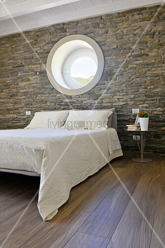 Double bed below porthole window in bedroom with stone wall