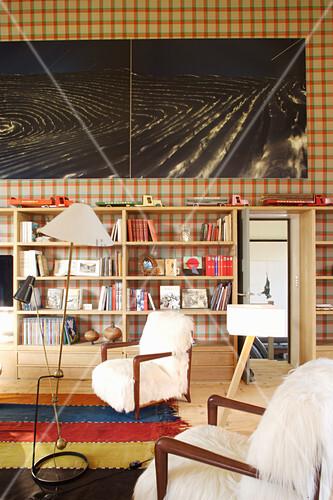 Armlehnstühle und Holzregal vor karierter Tapete in umgebautem Loft