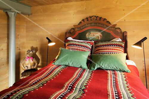 Doppelbett mit Ethno Accessoires im Schlafzimmer mit Holzverkleidung