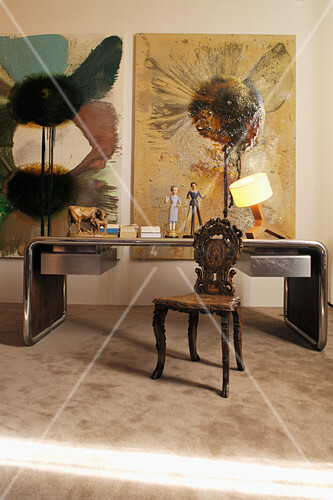 Desk with metal frame, antique carved wooden chair and modern artworks on wall