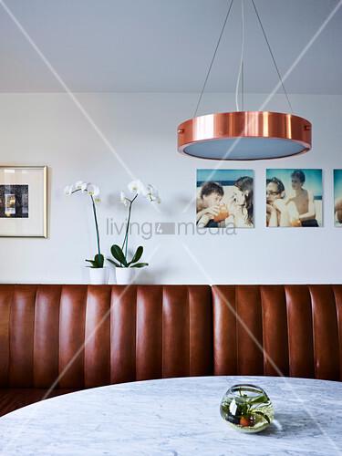 Brauner Leder-Sitzbank im Esszimmer, darüber Orchideen und Fotos an der Wand