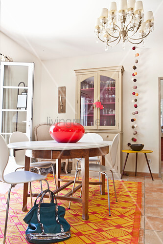 Round dining table with classic chairs on orange rug in front of dresser