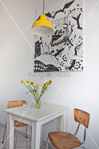 Small table and two chairs below yellow pendant lamp