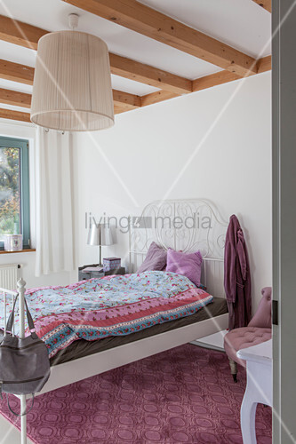 White metal bed in bright bedroom with wooden ceiling beams