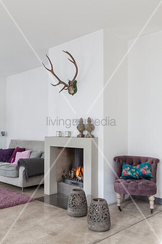 Lilac easy chair, fireplace and grey sofa in living room