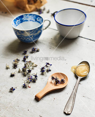 Dried flowers, spoon of honey and teacups