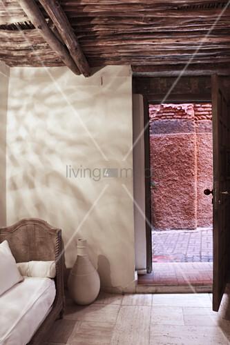 Blick vom Zimmer mit Holzdach durch die offene Tür auf die Straße