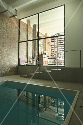 View from swimming pool into living room through internal glass wall