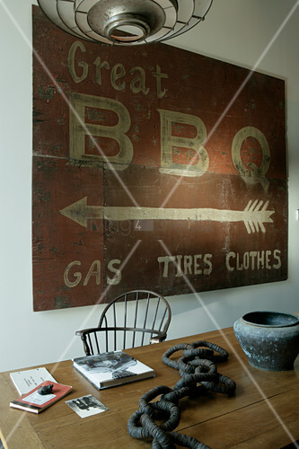 Old BBQ sign above artworks on wooden table