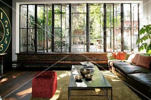 Sonniges Wohnzimmer mit Fensterfront zur Dachterrasse