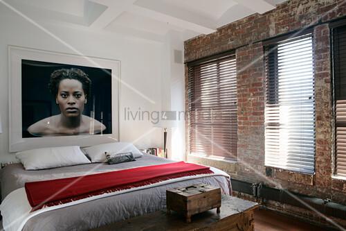 Foto einer Frau über dem Bett im Schlafzimmer mit Backsteinwand