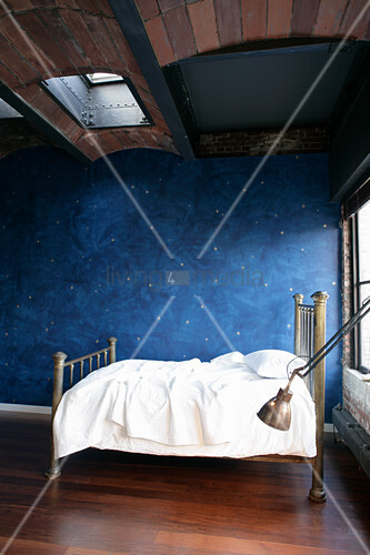 Child's bed against blue wall with pattern of stars below vaulted ceiling
