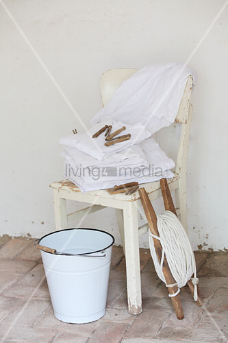 Dried vintage-style laundry on wooden chair, washing line on reel and enamel bucket