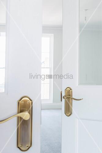Open double doors leading into empty white room