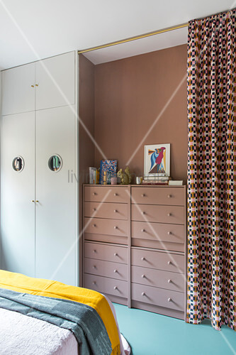 Brown, stacked chests of drawers against matching wall in bedroom