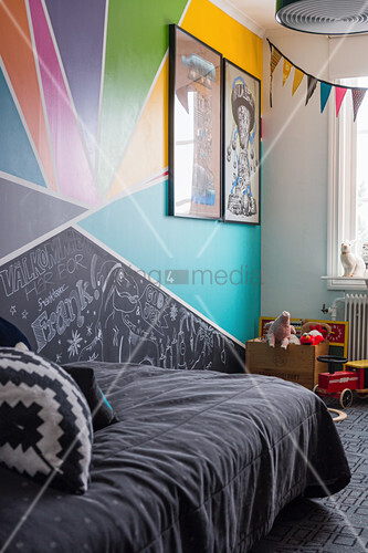 Dark bedspread on bed in child's bedroom with multicoloured wall
