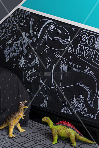 Toy dinosaurs in front of drawings on chalkboard in child's bedroom