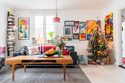 Coffee table in front of black leather sofa in living room with Christmas tree in corner and comic-style artworks on wall