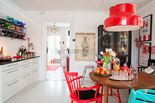Round table and chairs below red lampshade in white kitchen-dining room