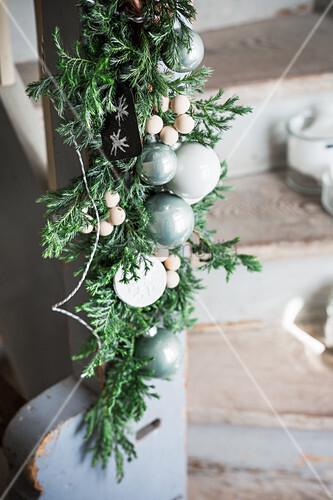 Girlande mit Wacholderzweigen, Holzperlen und Christbaumkugeln