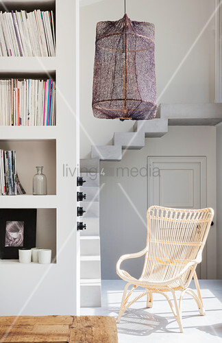 Rattan armchair in light-flooded spot at foot of stairs