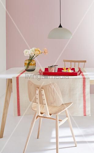 Naturfarbener Leinen-Tischläufer mit roter Bordüre auf Esstisch