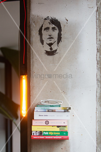 Stacked books on floating shelf, lamp and stencil portrait on wall