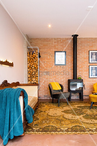 Log burner, retro armchair, stacked firewood and sofa in open-plan interior with brick wall