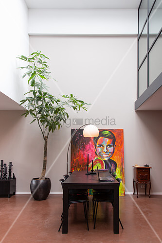 Dark wooden table and chairs, standard lamp, large painting and potted tree in interior with high ceiling