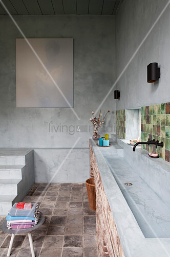Long sink in rustic bathroom with concrete walls