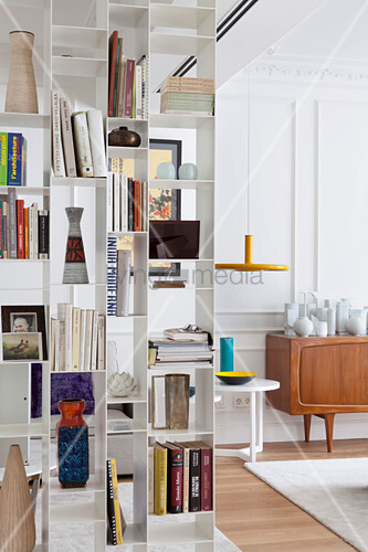 White, metal bookcase used as partition in living room