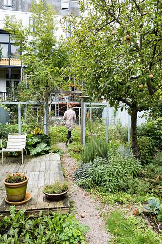 Frau geht durch naturnahen Garten mit verwitterter Terrasse