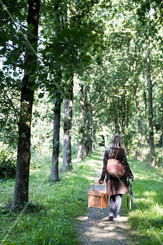 Frauen trägt Picknickkorb auf Weg durch Baumallee