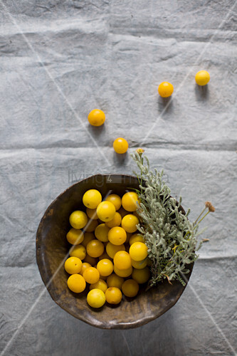 Bright yellow mirabelle plums in rustic wooden bowl on linen cloth