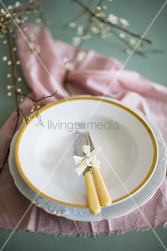 Cutlery with yellow handles on two plates on pink cloth