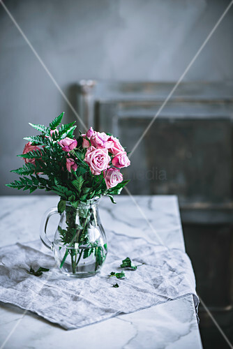 Bunch of pink roses in glass jug on table