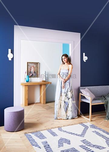 Junge Frau am Durchgang im Wohnzimmer mit blauer Wand