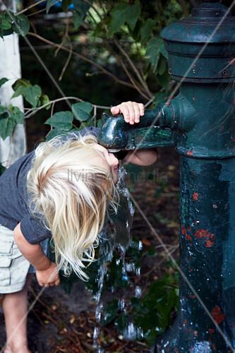 Blonder Junge trinkt am Brunnen